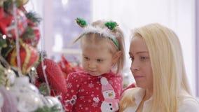 Una mujer que detiene a una pequeña hija en sus brazos en un árbol de navidad adornado metrajes