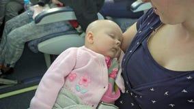 Una mujer que detiene a su niño en un avión metrajes