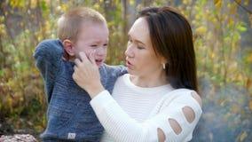 Una mujer que detiene a un adulto gritador del niño Retrato de dos, madre joven e hijo La madre joven conforta a su hijo, ella la almacen de metraje de vídeo