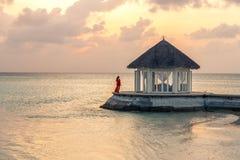 Una mujer que disfruta de una puesta del sol escénica en los Maldivas imagenes de archivo