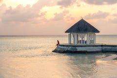 Una mujer que disfruta de una puesta del sol escénica en los Maldivas imagen de archivo
