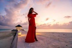Una mujer que disfruta de una puesta del sol escénica en los Maldivas fotografía de archivo libre de regalías