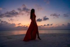 Una mujer que disfruta de una puesta del sol escénica en los Maldivas imagen de archivo libre de regalías