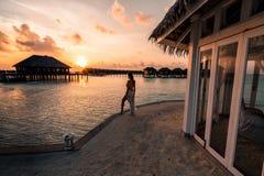 Una mujer que disfruta de una salida del sol en los Maldivas imagen de archivo