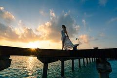 Una mujer que disfruta de una salida del sol en los Maldivas foto de archivo