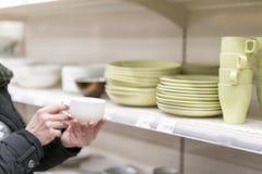 Una mujer que elige una taza en una tienda de la loza foto de archivo