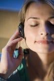 Una mujer que escucha la música Fotos de archivo libres de regalías