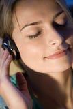 Una mujer que escucha la música Imagen de archivo libre de regalías