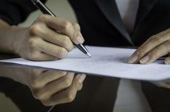 Una mujer que firma un contrato Fotografía de archivo