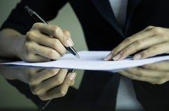 Una mujer que firma un contrato Imagen de archivo