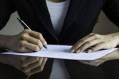 Una mujer que firma un contrato Foto de archivo