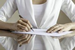Una mujer que firma un contrato Fotografía de archivo libre de regalías