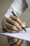 Una mujer que firma un contrato Imágenes de archivo libres de regalías