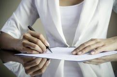 Una mujer que firma un contrato Imagenes de archivo