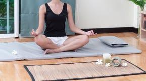 Una mujer que hace ejercicio de la yoga en la estera de la yoga Imágenes de archivo libres de regalías