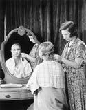Una mujer que hace el pelo de otra mujer (todas las personas representadas no son vivas más largo y ningún estado existe Garantía Imágenes de archivo libres de regalías