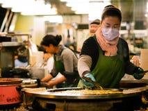 Una mujer que hace la tortilla original de la ostra del estilo en una cacerola grande en el distrito de las compras de la juventu imagen de archivo libre de regalías