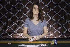 Una mujer que juega el póker en una tabla Imágenes de archivo libres de regalías