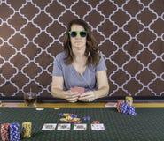 Una mujer que juega el póker en una tabla Imagen de archivo libre de regalías