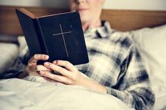 Una mujer que lee una biblia imagenes de archivo