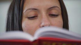 Una mujer que lee un libro rojo almacen de metraje de vídeo