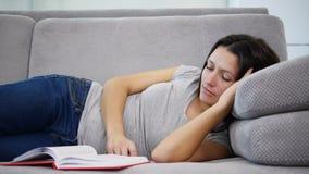 Una mujer que lee un libro rojo almacen de video