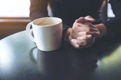 Una mujer que lleva a cabo la mano y que bebe el café caliente en café Foto de archivo