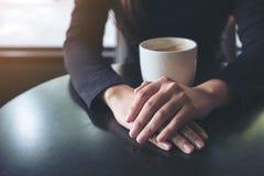 Una mujer que lleva a cabo la mano y que bebe el café caliente en café Foto de archivo libre de regalías
