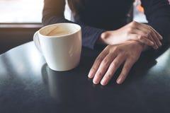Una mujer que lleva a cabo la mano y que bebe el café caliente en café Imagen de archivo libre de regalías