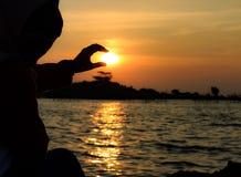 una mujer que lleva a cabo la puesta del sol Imagen de archivo libre de regalías