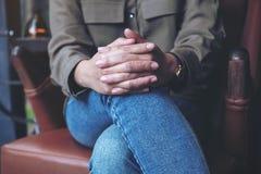 Una mujer que lleva a cabo sus manos mientras que se sienta en una butaca del cuero del vintage imagenes de archivo