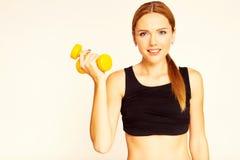 Una mujer que lleva a cabo una pesa de gimnasia amarilla Enganchado a aptitud Imagen de archivo libre de regalías