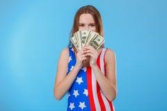 Una mujer que lleva monos con una impresión de la bandera americana lleva a cabo un manojo de billetes de dólar que ocultan detrá foto de archivo libre de regalías