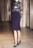 Una mujer que lleva una falda del lápiz de la blusa del diseñador y talones negros Imagen de archivo