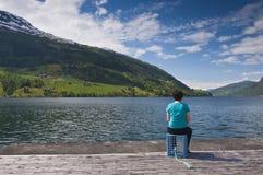 Una mujer que mira el lago Imagen de archivo libre de regalías