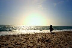 Una mujer que mira horizonte infinito en la costa Imagenes de archivo