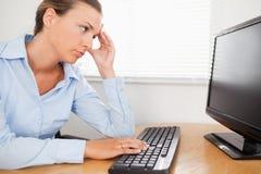Una mujer que mira a la PC-pantalla en oficina Foto de archivo libre de regalías