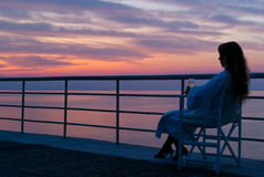 Una mujer que mira la puesta del sol colorida mítica Imagen de archivo