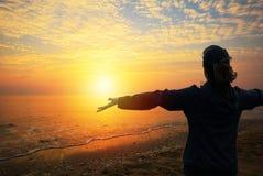 Una mujer que mira a la puesta del sol en la playa Imagenes de archivo