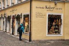 Una mujer que mira la ventana de la tienda Imagen de archivo libre de regalías