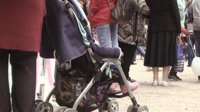 Una mujer que monta a un bebé en un cochecito almacen de video