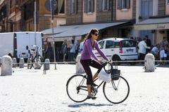 Una mujer que monta una bicicleta Imágenes de archivo libres de regalías