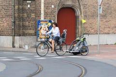 Una mujer que monta una bicicleta Foto de archivo