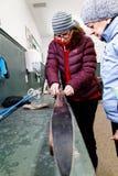 Una mujer que muestra a alguien cómo preparar los esquís del campo a través imagen de archivo libre de regalías