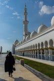 Una mujer que pasa por la mezquita magnífica Sheikh Al Zayed en Abu Dhabi Fotografía de archivo