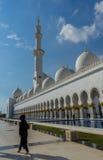Una mujer que pasa por la mezquita magnífica Sheikh Al Zayed en Abu Dhabi Imágenes de archivo libres de regalías