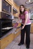 Una mujer que pone las galletas en horno Imagenes de archivo
