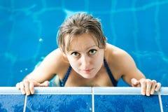 Una mujer que presenta en la piscina que lleva a cabo el borde - actividad deportiva foto de archivo