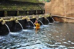 Una mujer que ruega en las aguas santas del templo de Tirta Empul en Bali Foto de archivo libre de regalías