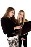 Una mujer que señala en la computadora portátil que muestra a la otra mujer Fotos de archivo